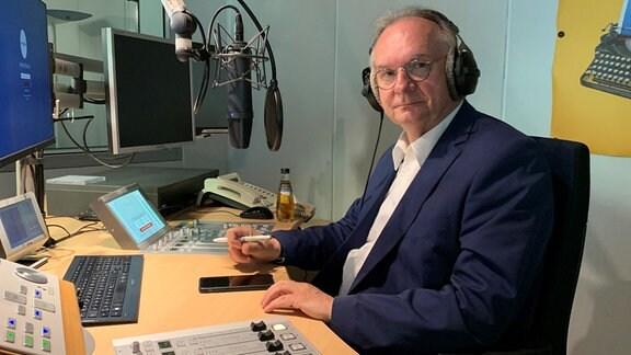 CDU-Spitzenkandidat Reiner Haseloff sitzt in einem Hörfunkstudio und lächelt in die Kamera.
