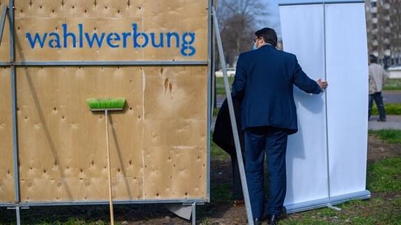 Tobias Krull (CDU), Kandidat für die Landtagswahl, stützt vor der Vorstellung der Wahlplakatkampagne der CDU Sachsen-Anhalt ein Plakat