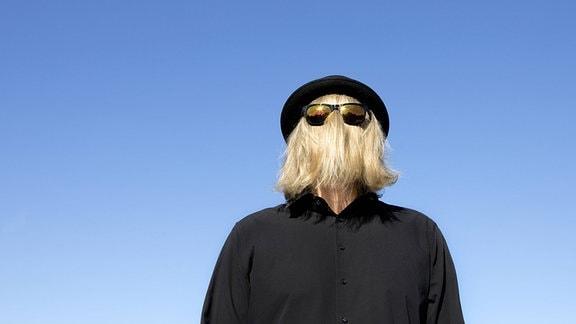 Ein Mann bedeckt sein Gesicht mit blonden Haaren und Sonnenbrille