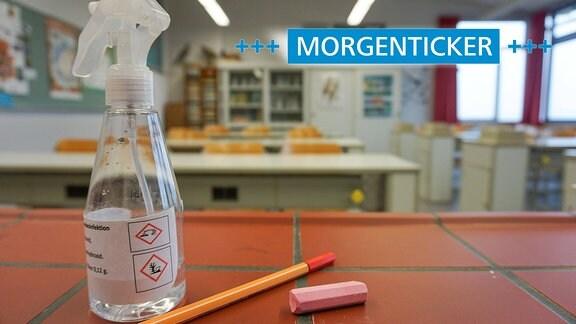In einem Chemie- Klassenraum einer Schule liegt ein Stueck Kreide, ein Stift und eine Sprühflasche, die mit Desinfektionsmittel gefuellt ist, auf einem Tisch.