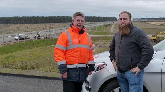 Zwei Männer an einer Autobahnbaustelle.