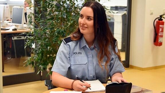 Eine junge Frau in Polizeiuniform sitzt an einem Tisch und schreibt