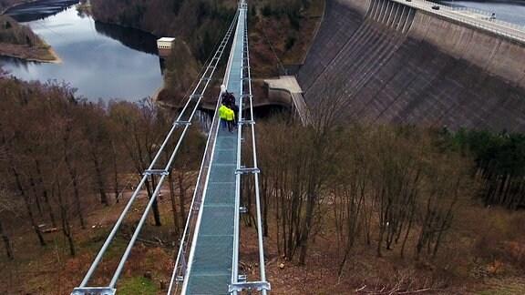 Menschen laufen auf der Fußgänger-Seilhängebrücke, die das Rappbodetal neben der gleichnamigen Talsperre überspannt