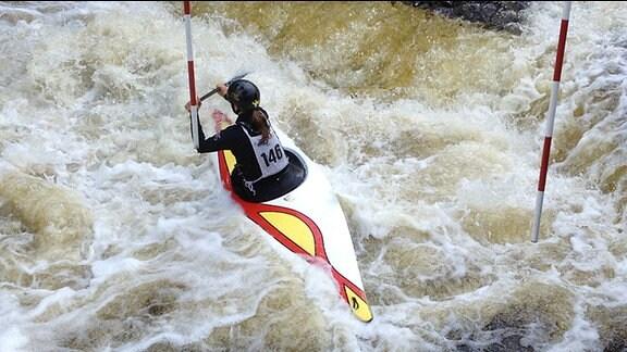 Eine Slalomkanutin im Wasserstrudel