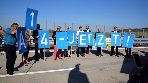 """Menschen halten Schilder, auf denen steht """"A14 jetzt"""""""