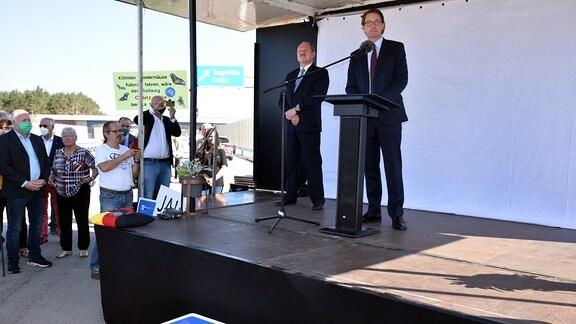 Landesverkehrsminister Webel und Bundesverkehrsminister Scheuer stehen auf einer Bühne