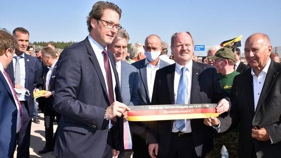 Landesverkehrsminister Webel und Bundesverkehrsminister Scheuer halten ein Stück Band in den Händen