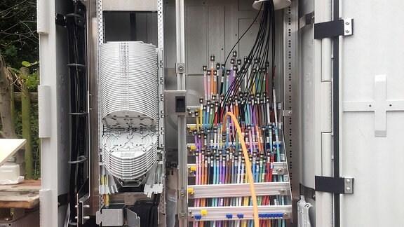 Viele kleine bunte Plastikrohre in einer Art Stromkasten.