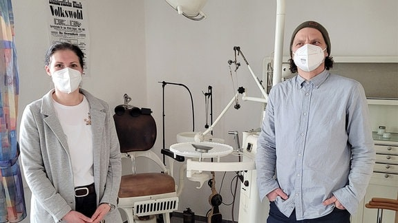 Eine junge Frau und ein Mann stehen mit Masken vor einem alten Behandlungsstuhl für Zahnärzte.