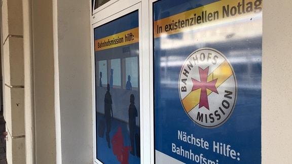 """Ein Schild mit der Aufschrift """"Bahnhofsmission hilft in existenziellen Notlagen"""" steht in einem Fenster."""