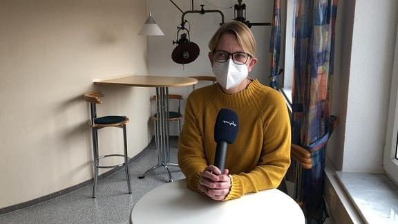 Eine Frau mit einem gelben Pullover und einer Maske steht an einem Tisch und erklärt etwas.