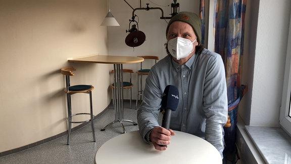 Ein Mann mit Mütze, blauem Hemd und Maske steht an einem Tisch und spricht Richtung Kamera.