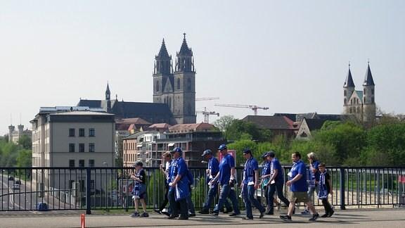 FCM-Fans laufen zum Stadion, im Hintergrund die Kulisse des Doms.