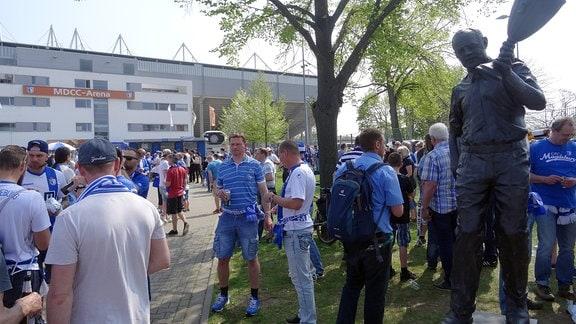 Fans vor dem Stadion, rechts steht eine Statue.