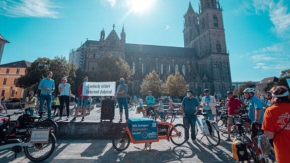 Teilnehmer einer Fahrraddemo demonstrieren vor dem Dom in Magdeburg. Sie halten ein Transparent in die Höhe.