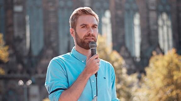 Benjamin Gehne, Gründer von Gemeinsam Handeln, spricht vor dem Dom in Magdbeurg zu Teilnehmern einer Demonstration.