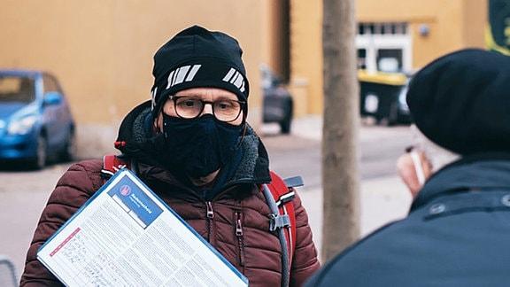 Ein Mann mit Mütze und Corona-Maske sammelt Unterschriften für einen Bürgerentscheid zum Thema sicherer Radverkehr in Magdeburg.