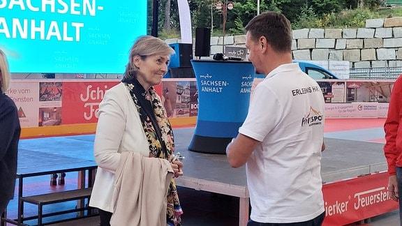 Eine Frau vor einer Leinwand, auf der MDR Sachsen-Anhalt steht, in intensivem Gespräch mit einem Mann, auf dessen T-Shirt für Erlebnisse im Harz geworben wird.