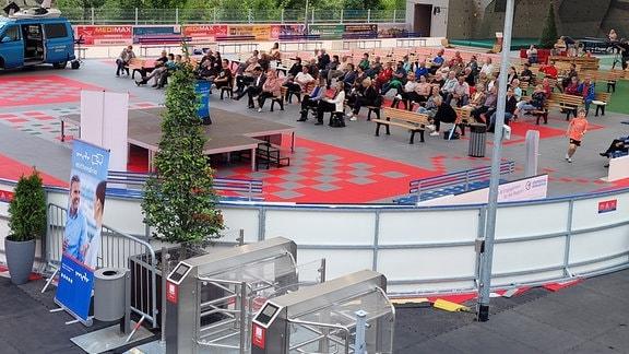 Eine Arena mit Holzbänken und etwa 60 Zuschauern, die auf eine Leinwand schauen, von oben.