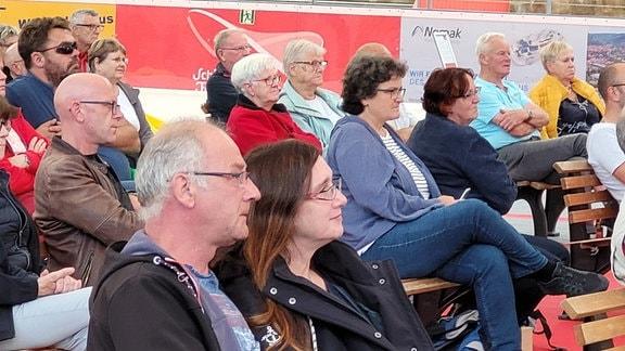 Zuschauer auf Holzbänken, die mit konzentrierten und bewegten Blicken auf eine Leinwand schauen.