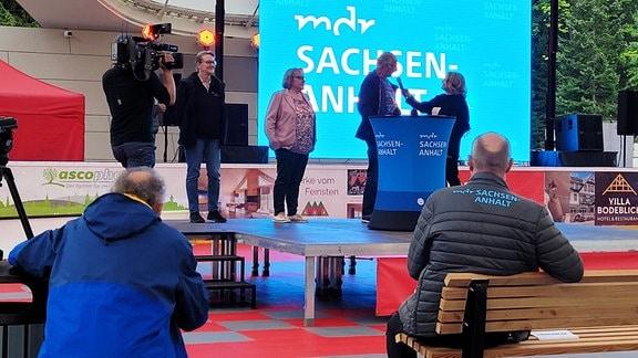 Mehrere Personen werden vor einer Leinwand, auf der MDR Sachsen-Anhalt steht, auf einer Bühne interviewed.