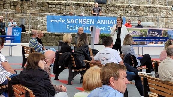 Zuschauer auf Holzbänken lauschen den Worten der MDR Intendantin Karola Wille, die vor einem MDR-Banner vor dem Publikum steht.