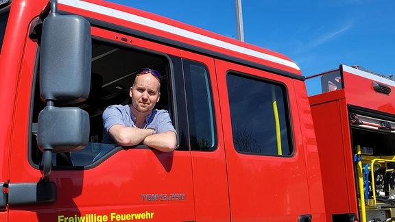 Ein Mann guckt aus einem Feuerwehrauto