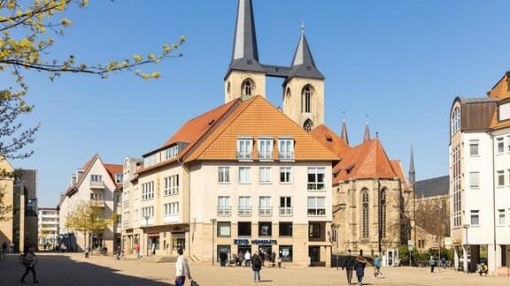 Blick auf einen belebten Platz in der Innenstadt von Halberstadt. Im Bildhintergrund stehen mehrere Gebäude.
