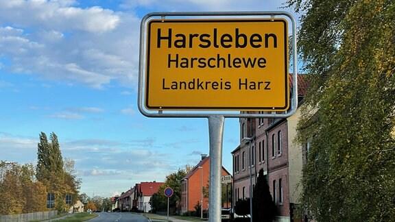 Auf einem gelben Ortseingangsschild sind die Begriffe Harsleben und Harschlewe zu sehen.