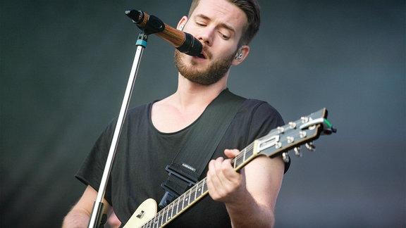 Musiker spielt Gitarre und singt ins Mikrofon.