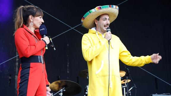 Moderatorin Susi Brand und Beatboxer Mando stehen auf der Bühne.