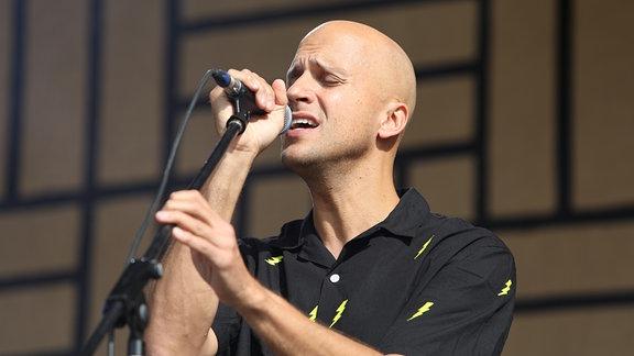 Sänger Milow am Mikrofon auf der Bühne