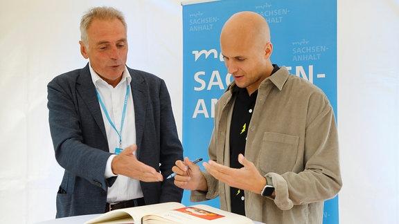 Oberbürgermeister Peter Gaffert und Milow beim Eintrag ins goldene Buch der Stadt Wernigerode