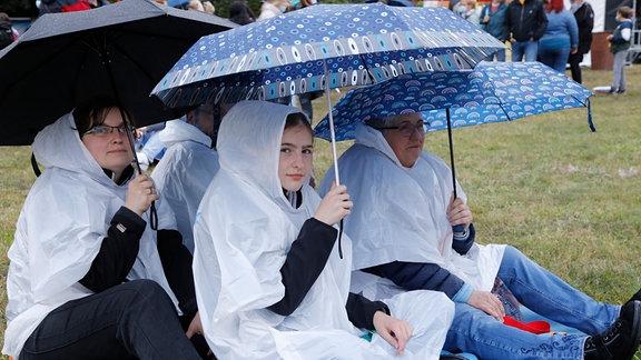 Besucherinnen sitzen mit Regenschirmen auf einer Decke.
