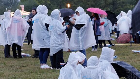 Besucher mit Regencaps auf einer Wiese