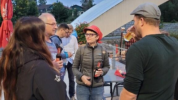 Mehrere Menschen auf einer Terrasse in intensivem Gespräch.