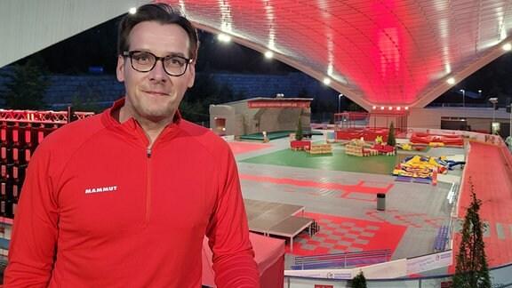 Ein Mann mit einem roten Funktionshirt steht erhöht am Rand einer rot ausgeleuchteten Arena und lächelt in die Kamera.