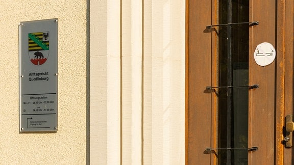 Neben einer Tür hängt ein Schild, das auf den Eingang des Amtsgerichts in Quedlinburg im Harz hinweist.
