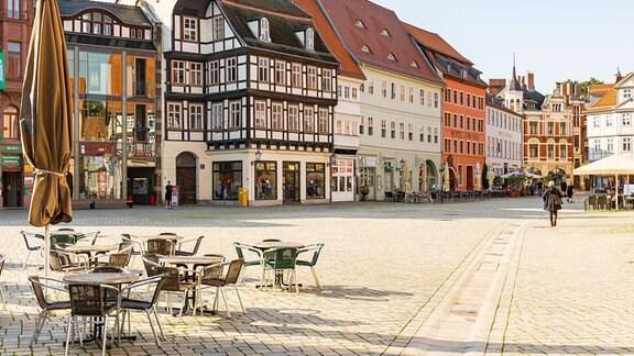 Auf dem Marktplatz von Quedlinburg stehen mehrere Tische und Stühle.