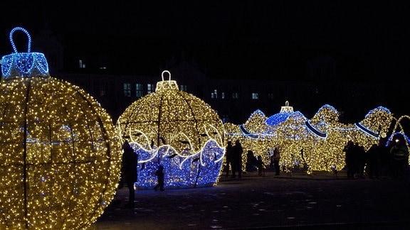 Funkelnde und leuchtende rieisge Weihnachtskugeln und Pferde, aus Lichterketten geformt, stehen auf dem Domplatz in Magdeburg.