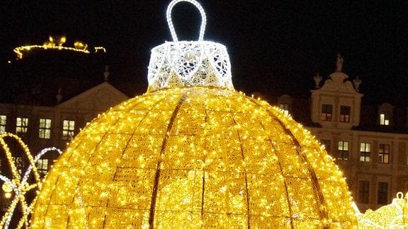 Eine riesige, golden leuchtende Christbaumkugel, aus Lichterketten geformt.