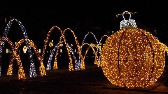 Funkelnde und leuchtende rieisge Weihnachtskugeln und Pferde, aus Lichterketten geformt, stehen auf dem Domplatz in Magdeburg. Drum herum Dunkelheit. Dahinter leuchtende Bögen.