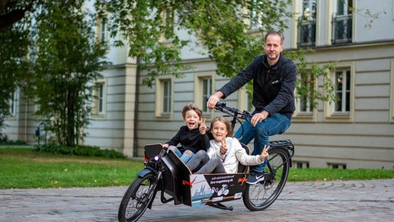 Ein Mann fährt mit einem Lastenrad um die Kurve. In dessen Korb sitzen zwei strahlende Kinder.