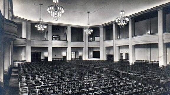 Der zum Konzertsaal bestuhlte Magdeburger Kristallpalast mit Kronleuchtern und viel Platz auf einer alten Schwarzweißaufnahme