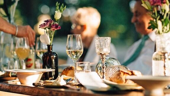 Ein festlich gedeckter Tisch mit Weingläsern, im Hintergrund verschwommen eine blonde Frau und ein Mann