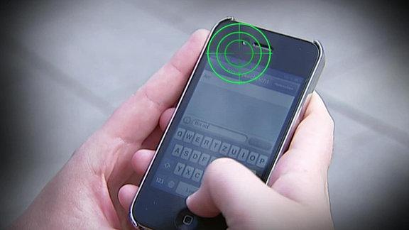 Auf einem Handy ist ein Chat-Programm geöffnet. Darüber schwebt ein Fadenkreuz.