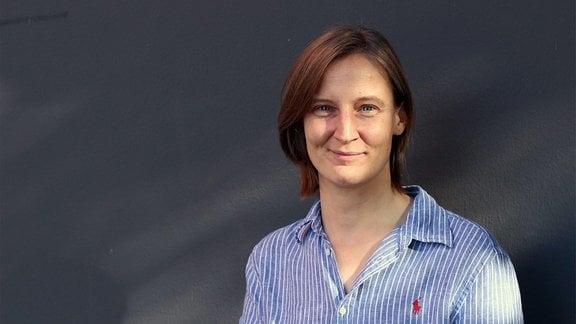 Eine brunette Frau in blauem Hemd steht vor einer grauen Wand