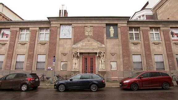 Ein renovierungsbedürftiges Gebäude mit einem Ausstellungsplakat.