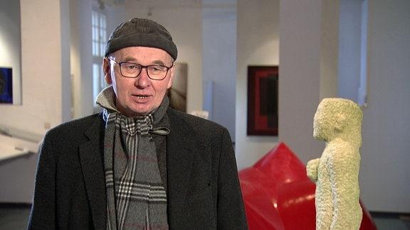 Ein Mann mit Brille und Mütze in einer Galerie.