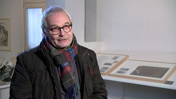 Ein Mann mit Brille und Winterjacke in einer Galerie